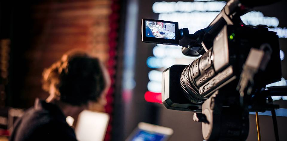 Filming creative video footage with professional video camera during the night